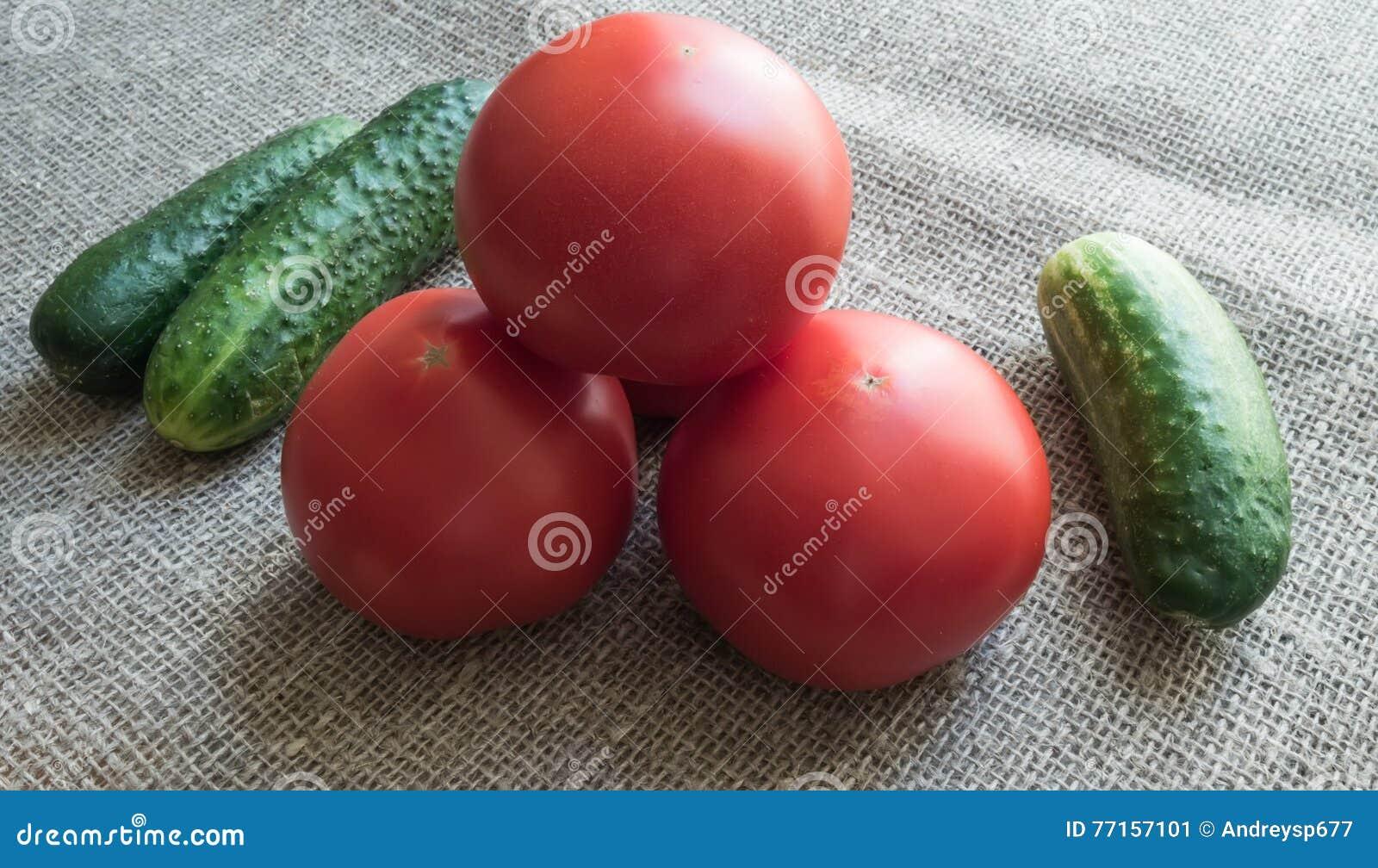 Concombres verts et tomates rouges sur la toile de jute