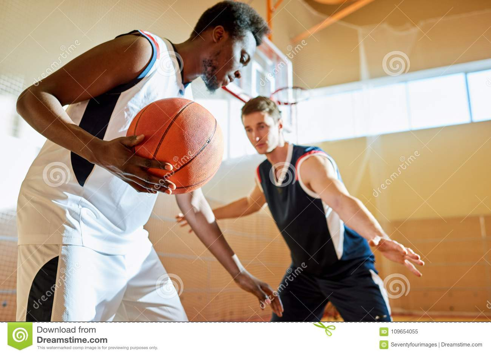 Concorrentes novos que jogam o basquetebol na corte do treinamento
