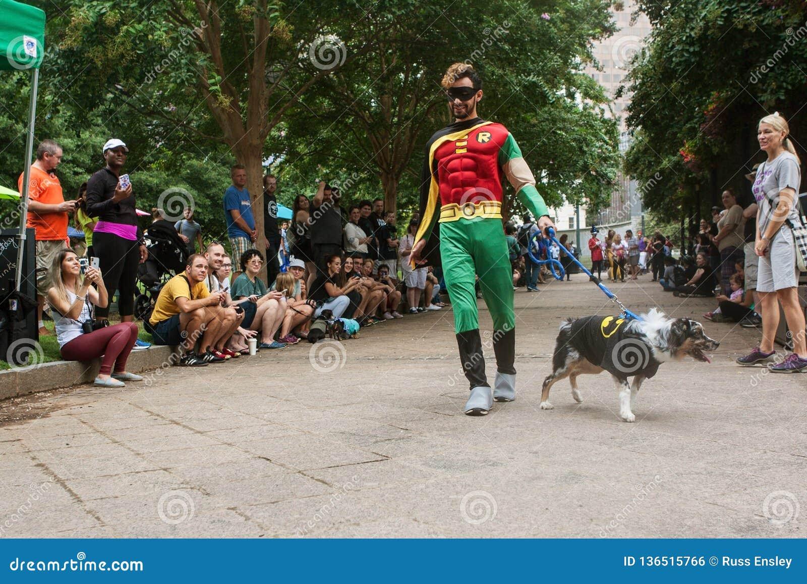 Concorrenti che indossano raggiro di Robin Costumes Participate In Doggy e di Batman
