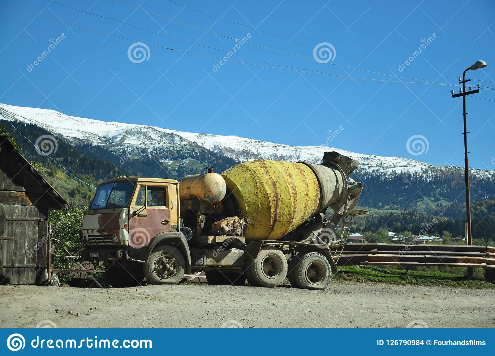 Concrete mixer on the background of beautiful mountains