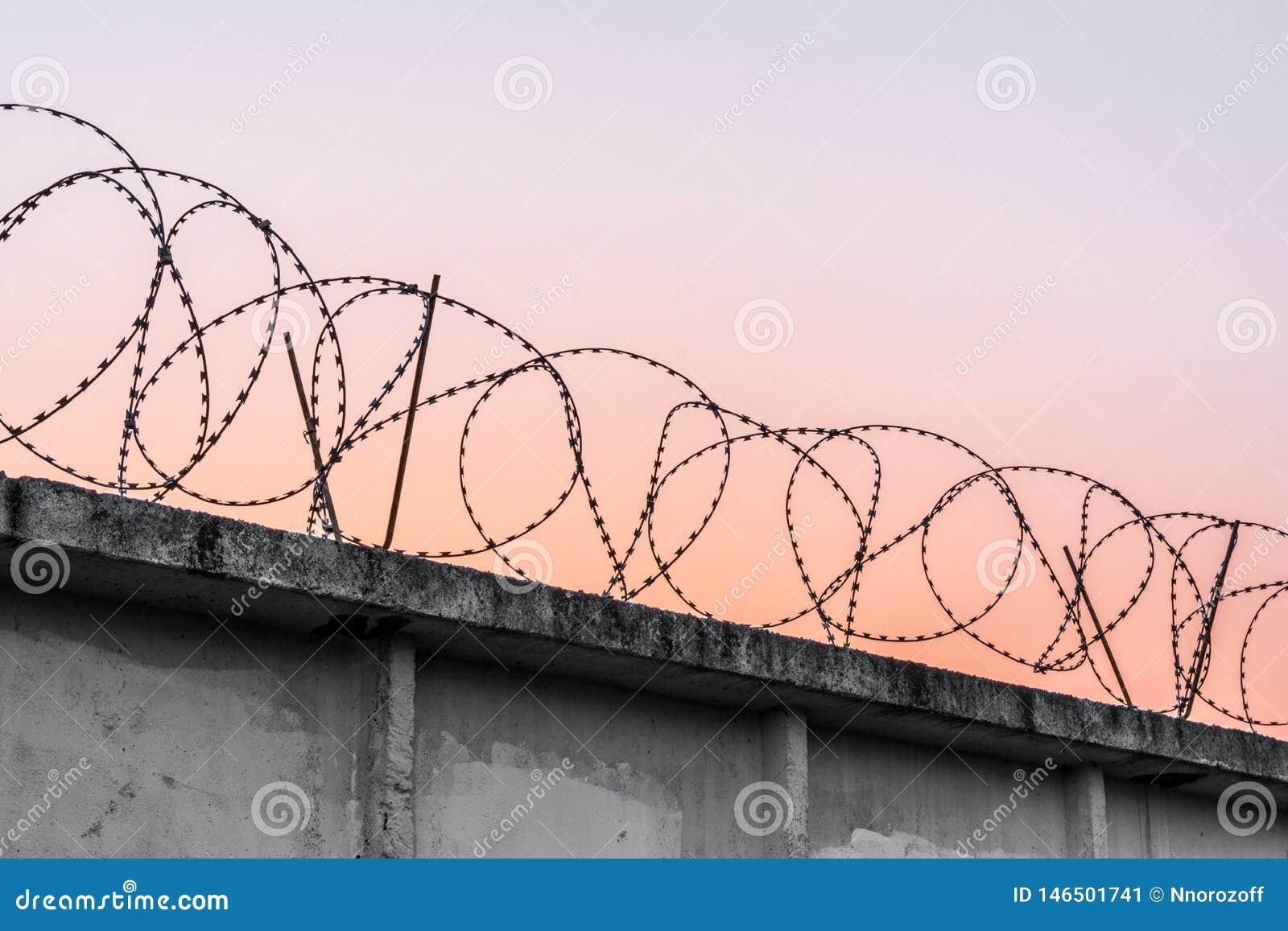 Concrete muur met prikkeldraad tegen een blauwe oranje avondhemel