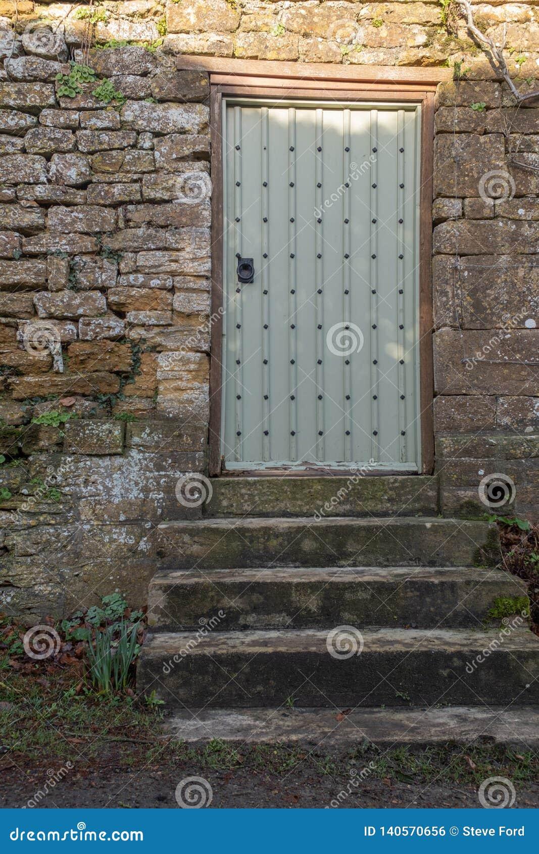 Concrete stappen die aan een beslagen deur ingebed in een muur leiden