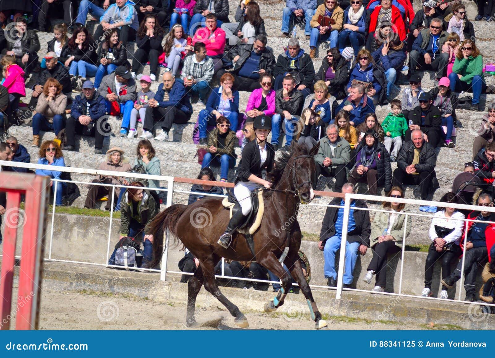 Cheval et spectateurs galopants d équitation de jeune fille au fond à la  concurrence d équitation pour des débutants et de jeunes cavaliers à  l occasion des ... 8c2c03da746