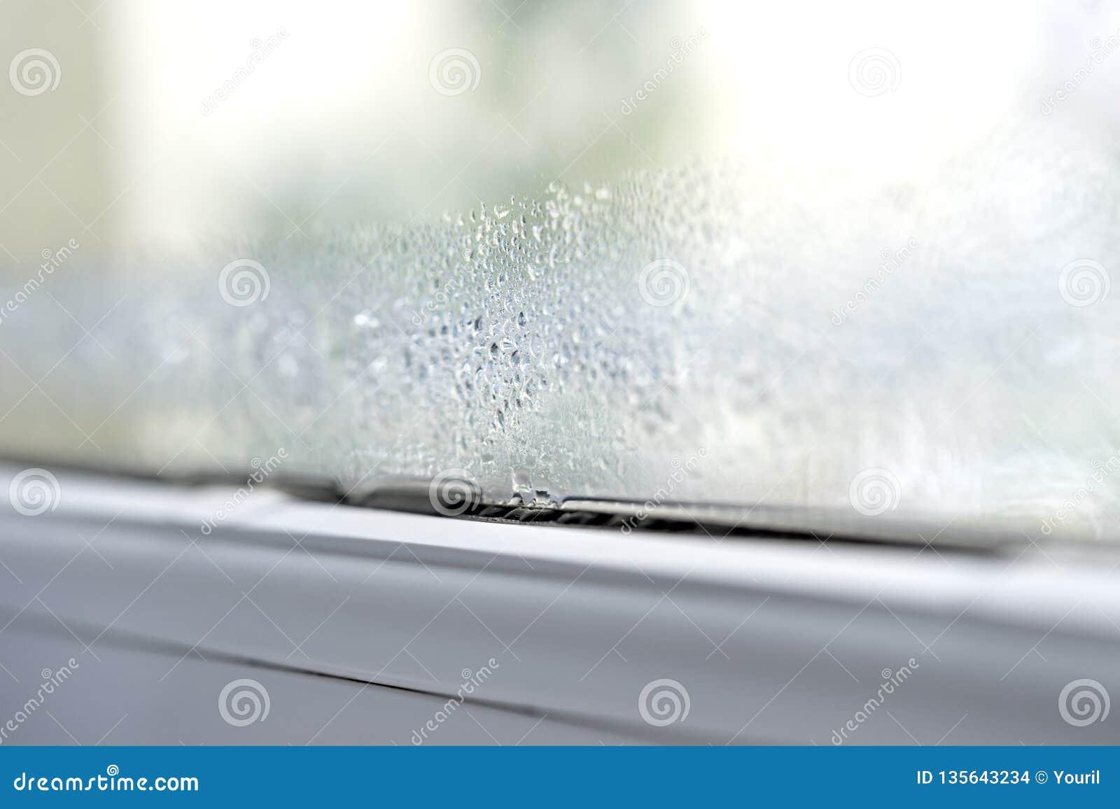 Condensación en la doble vidriera del primer de las ventanas de cristal del pvc