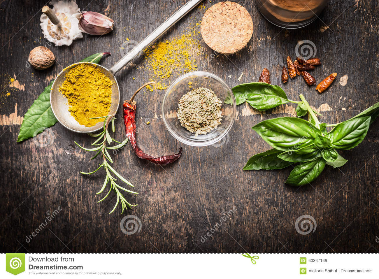 Condiments and spices for creative cooking on dark rustic wooden background, top view