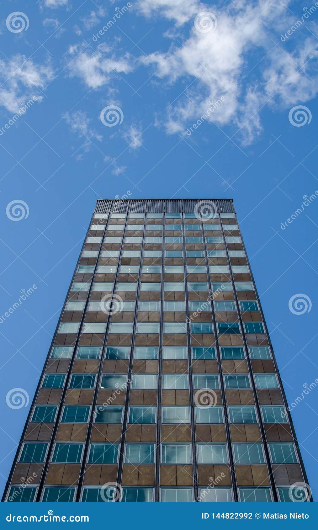 Condizione alta dell edificio per uffici sola sotto un cielo blu soleggiato con una coppia di coulds
