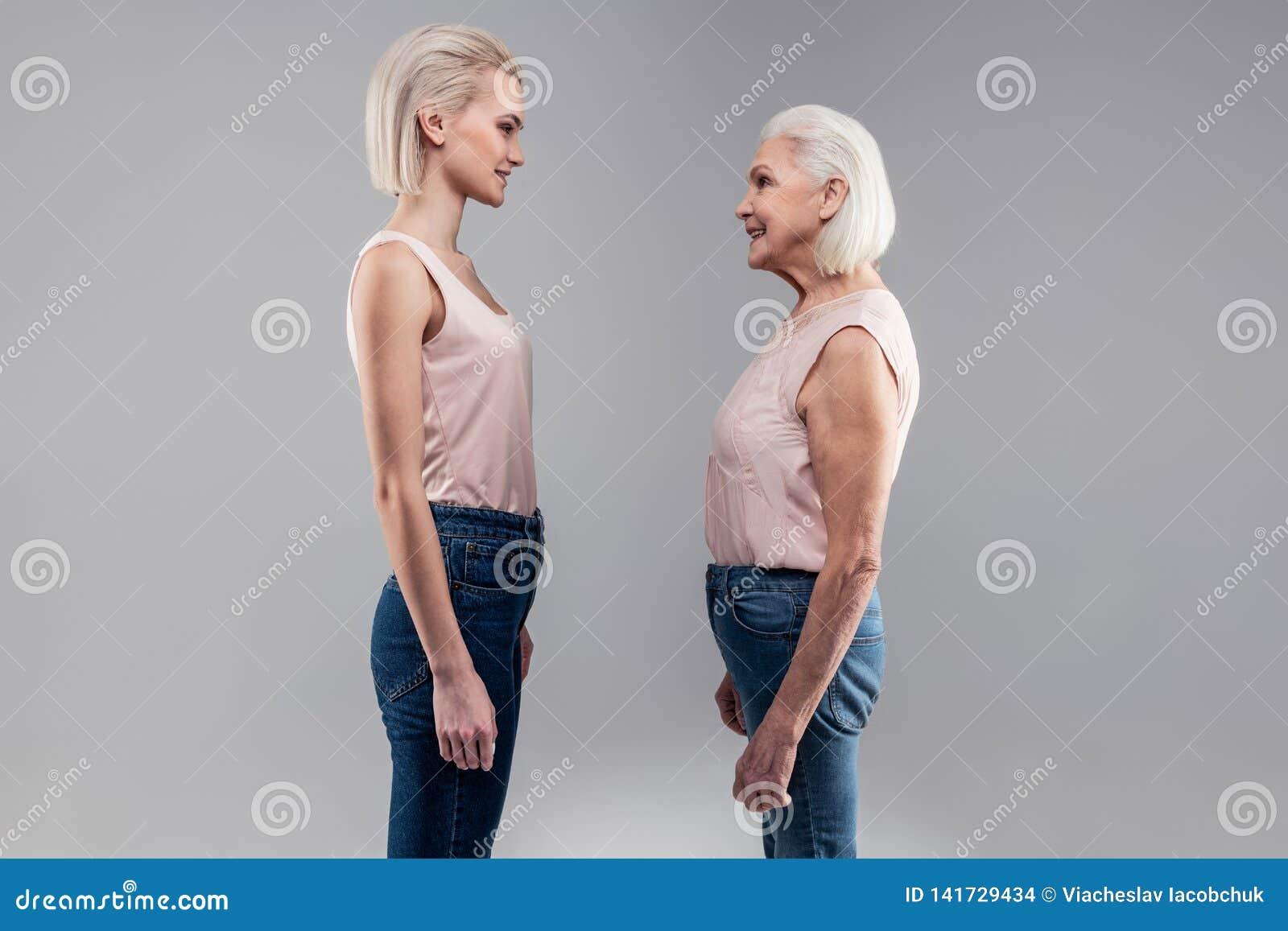 Condizione bionda dai capelli corti sorridente della giovane signora davanti al suo auto anziano