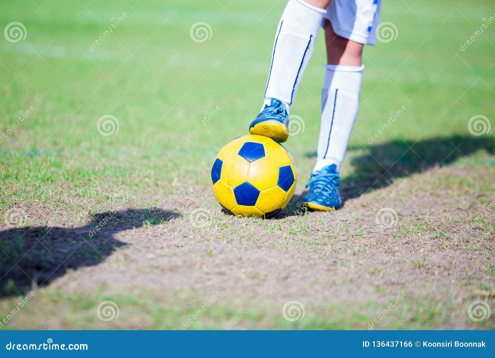 Condizione del giocatore di football americano del bambino e fare un passo sulla palla