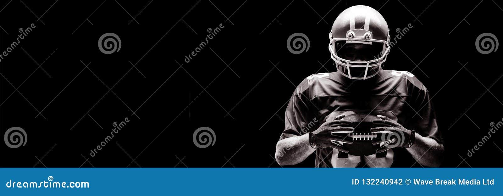 Condizione del giocatore di football americano con il casco e la palla di rugby