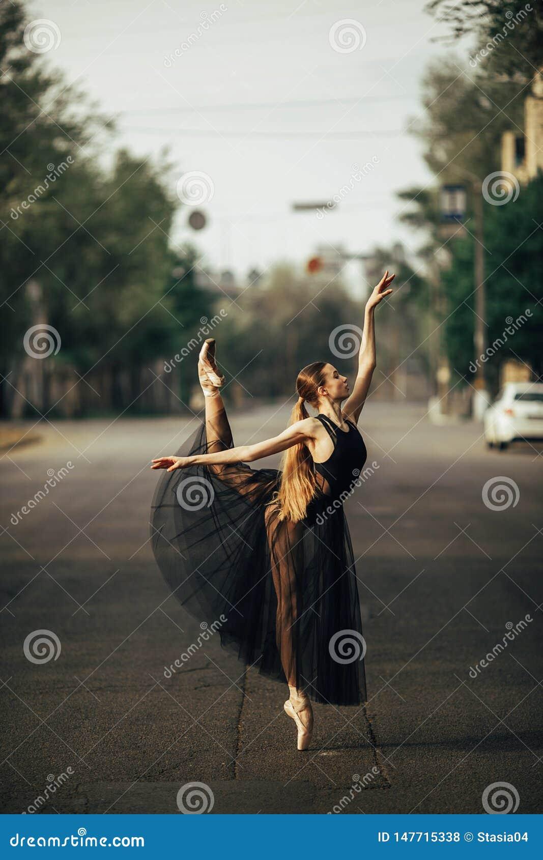 Condizione della ballerina nella posa di arabesque contro lo sfondo della via della città