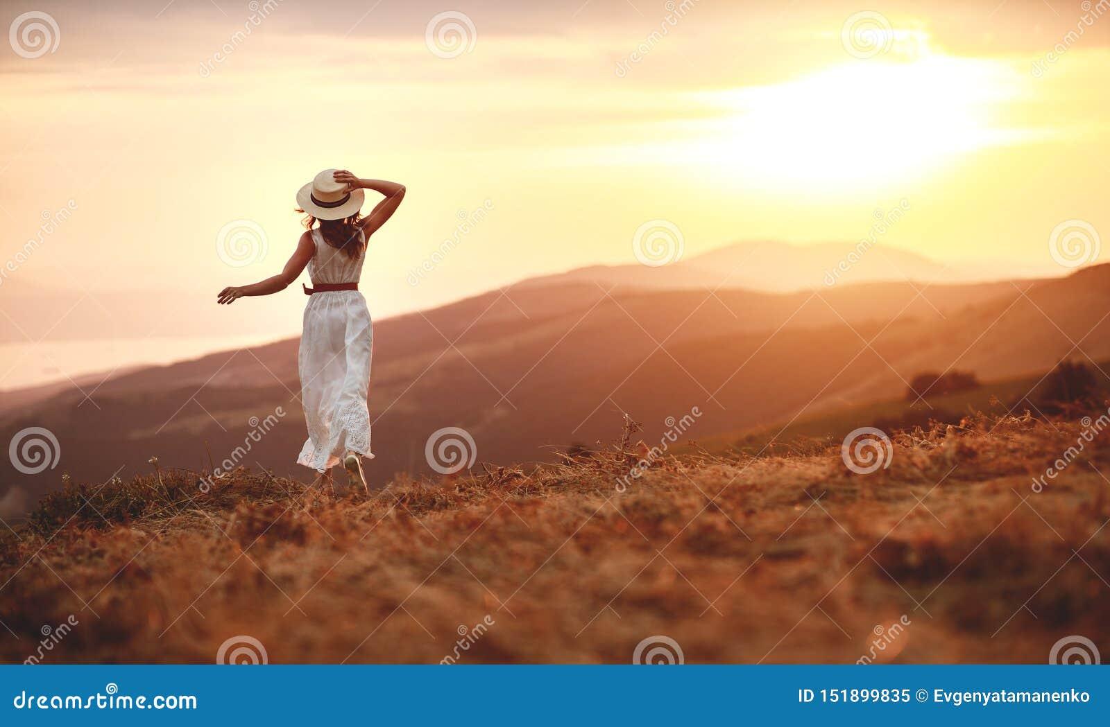 Condizione felice della donna con la sua parte posteriore sul tramonto in mani aperte del iwith della natura
