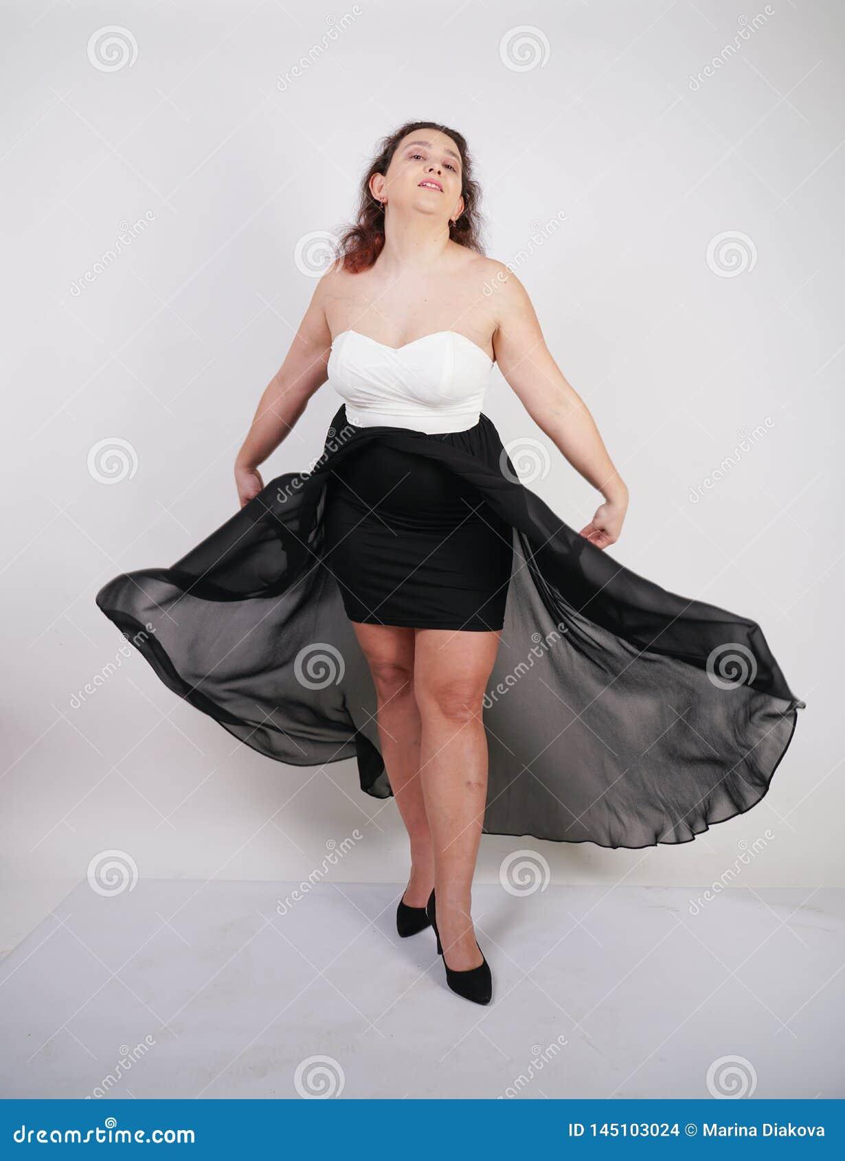 Condizione felice paffuta affascinante della donna in vestito uguagliante volante sul fondo bianco dello studio da solo