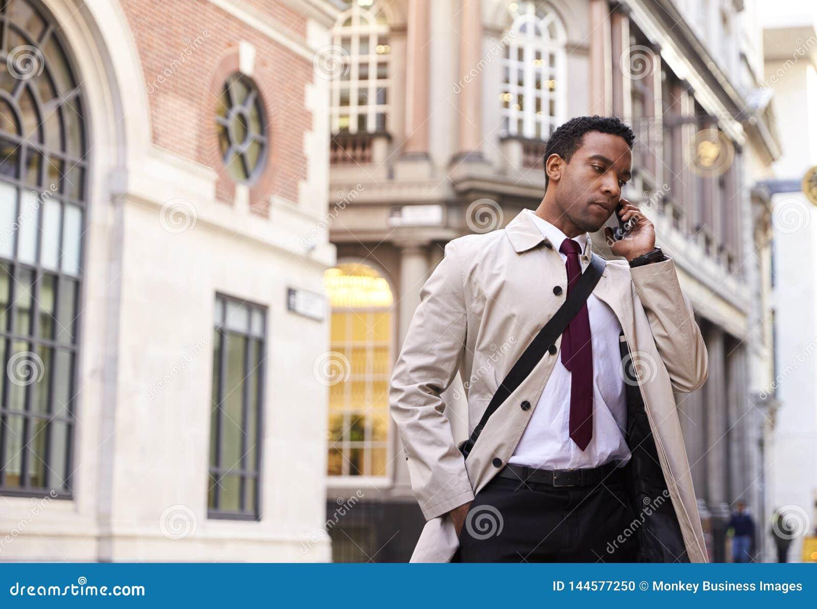 Condizione nera millenaria su una via a Londra che parla sul suo telefono, angolo basso dell uomo d affari