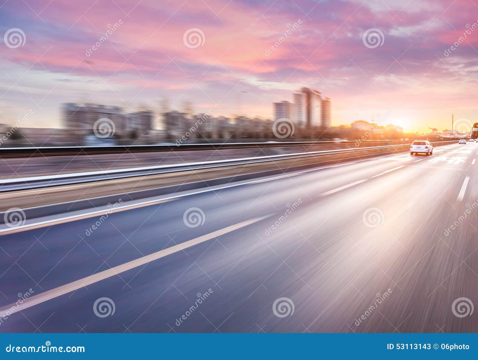 Condução de carro na autoestrada no por do sol, borrão de movimento
