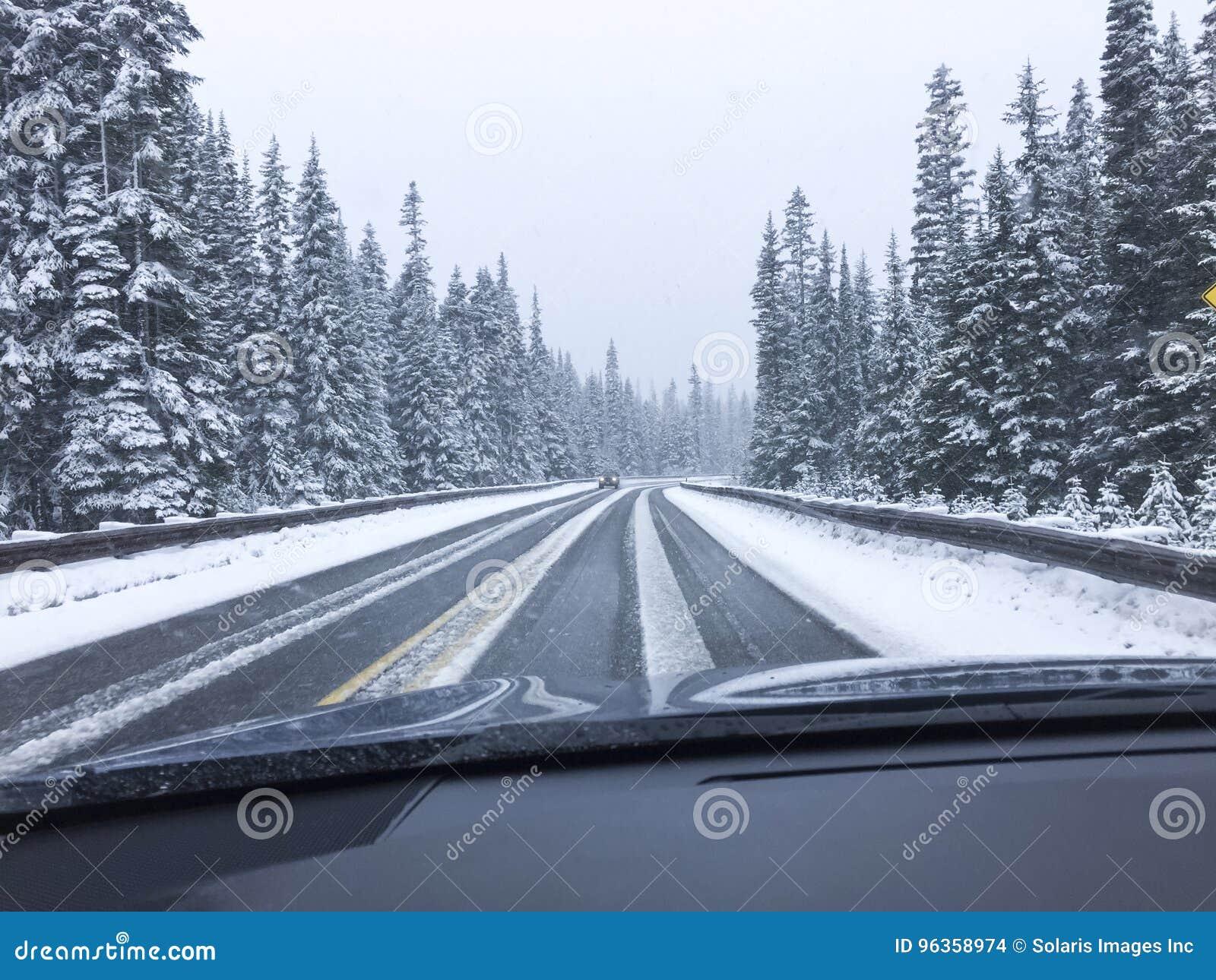 Condução de carro na estrada nevado coberto de neve da montanha na neve do inverno Ponto de vista do ponto de vista do ` s do mot