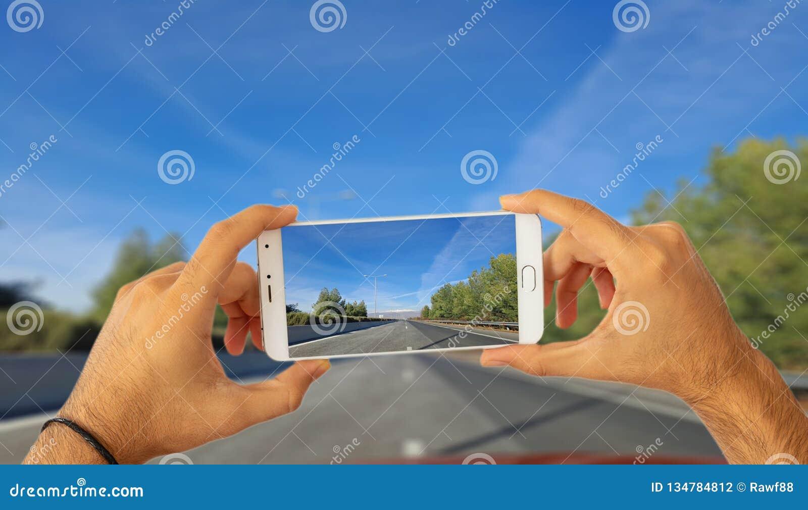 Condução e conceito dos telefones Mãos que guardam um smartphone, tomando uma foto no fundo da estrada do borrão ilustração 3D