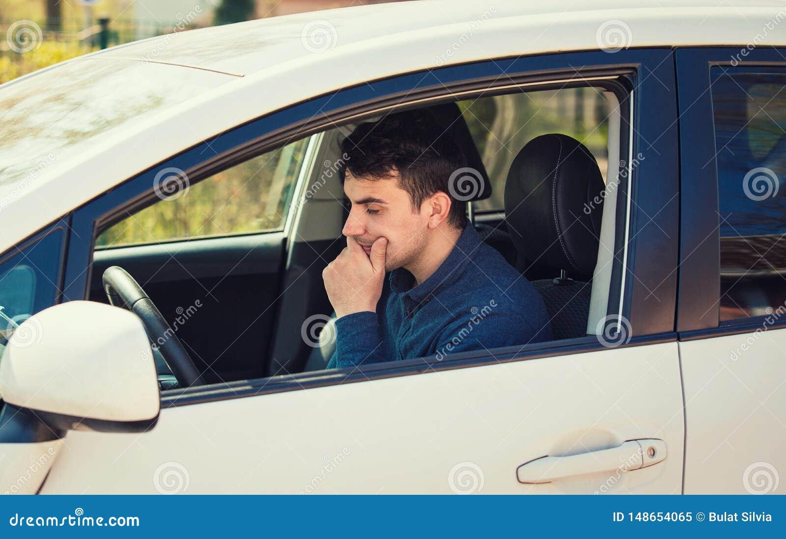 Conducteur réfléchi de jeune homme tenant sa main sous le menton semblant l attente soucieuse dans sa voiture