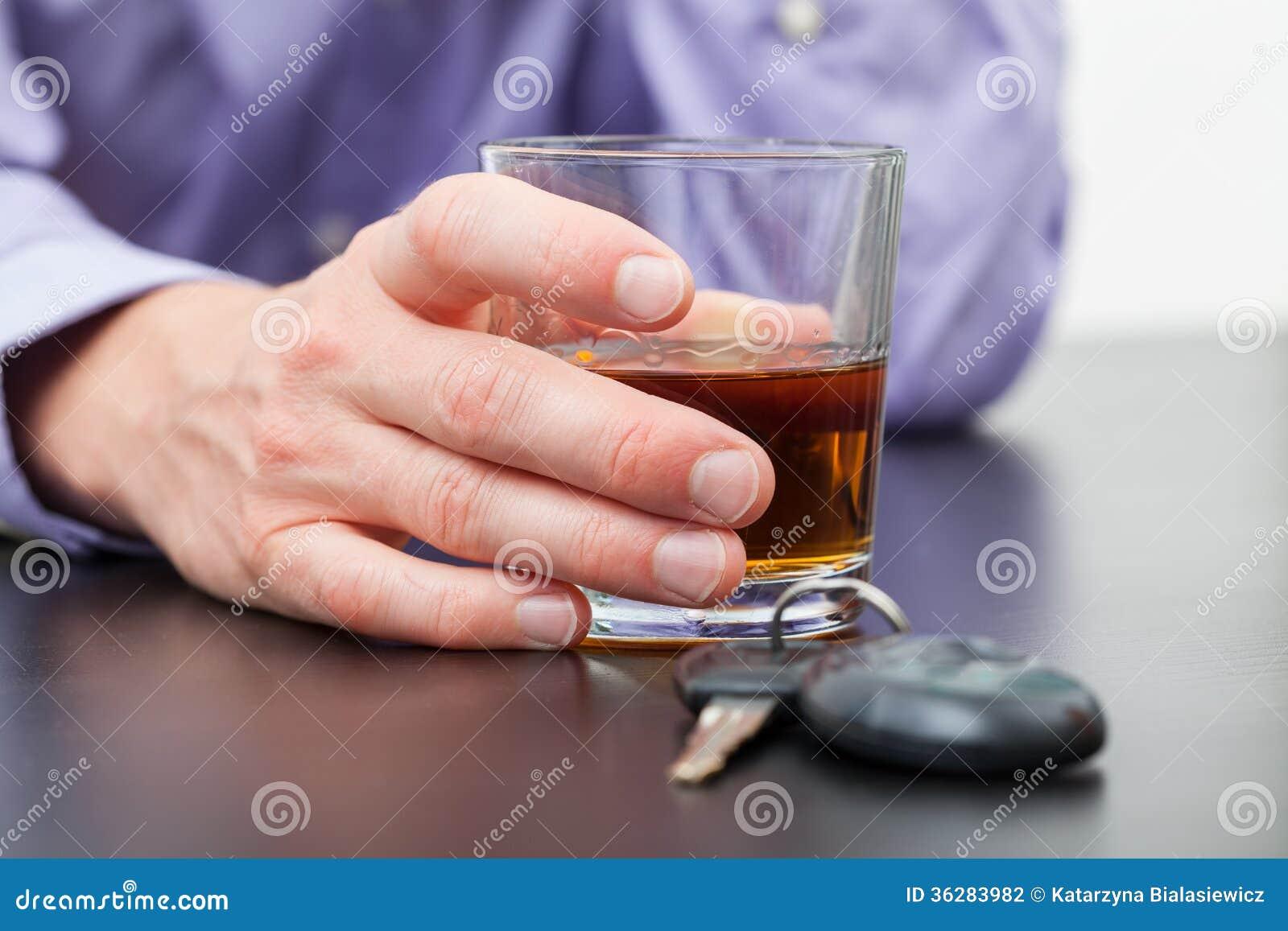 Conductor con el vidrio de whisky