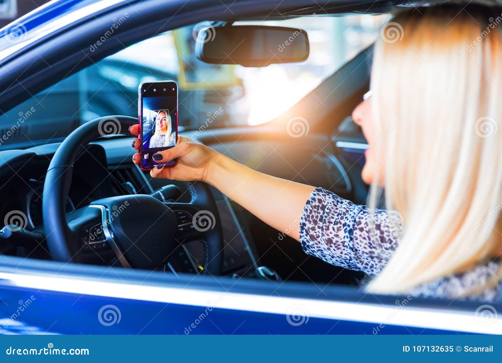 Conductor de la mujer joven que toma un selfie en su coche