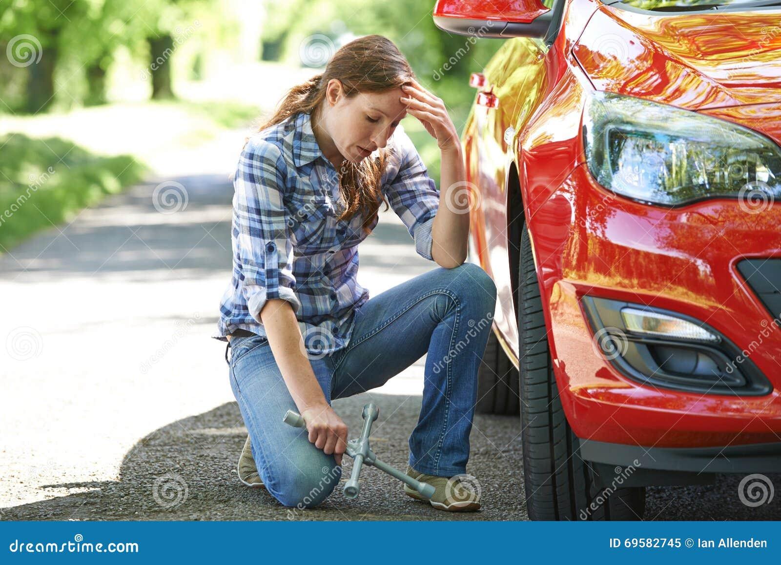 Conductor femenino frustrado With Tyre Iron que intenta a la rueda de cambio