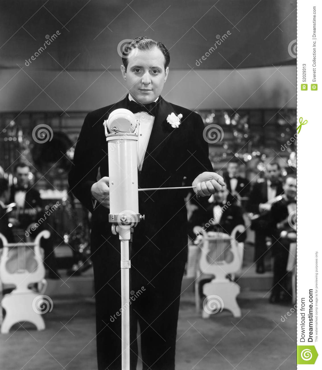 Conductor standing in front of his orchestra with a baton