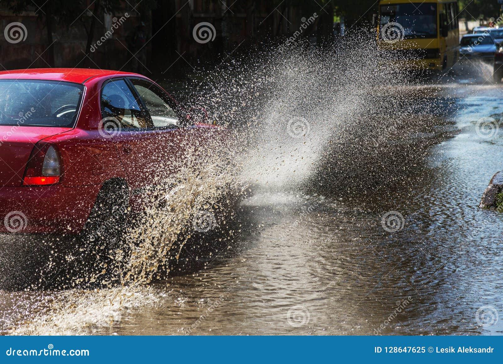 Conduire des voitures sur une route inondée pendant les inondations provoquées par la pluie fulmine Flotteur de voitures sur l ea