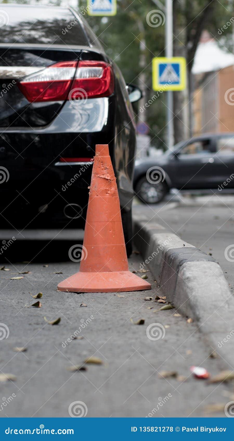 Cone velho alaranjado do tráfego na estrada perto de um cuidado
