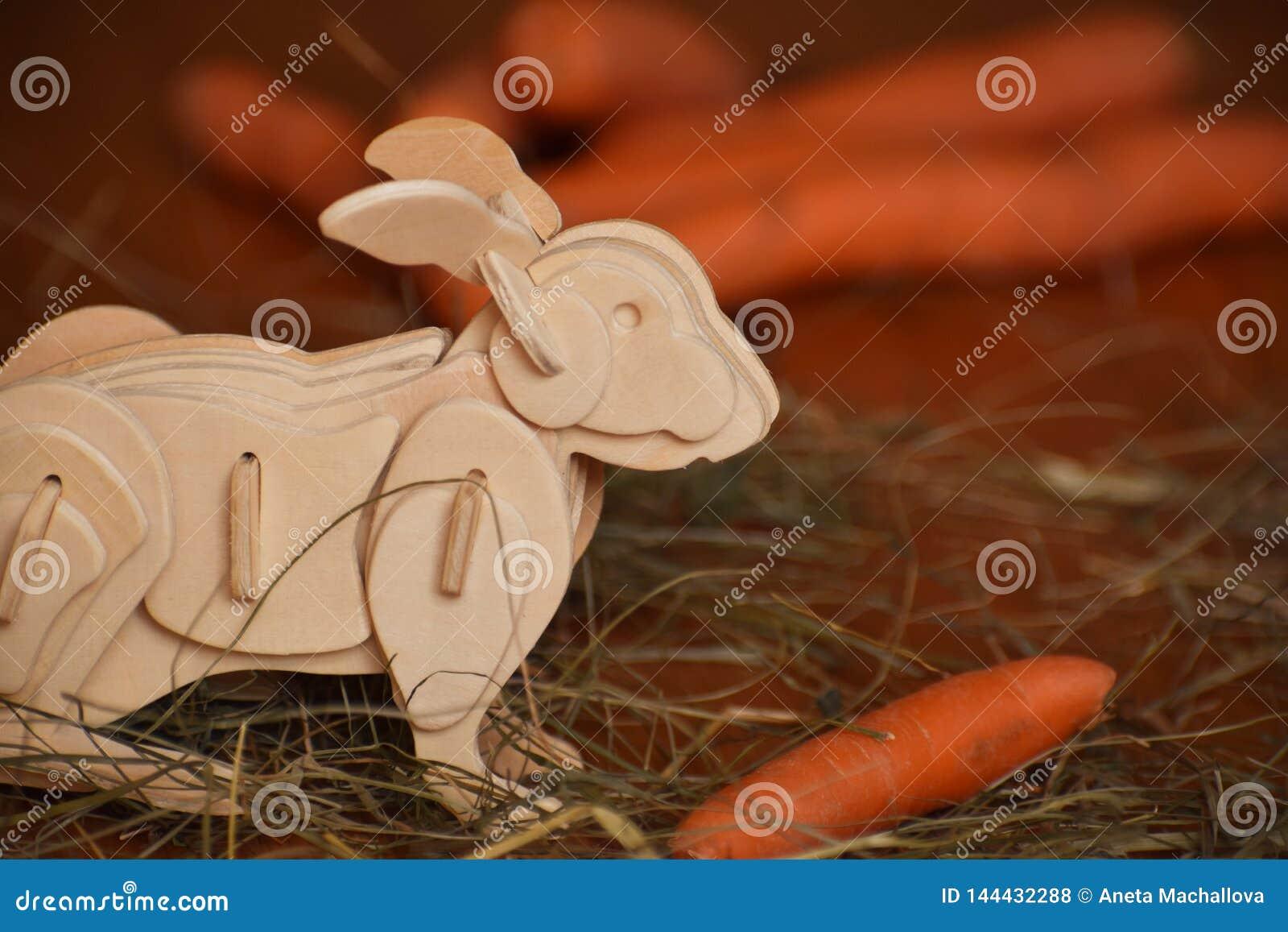 Conejito de madera del conejo con la zanahoria en heno