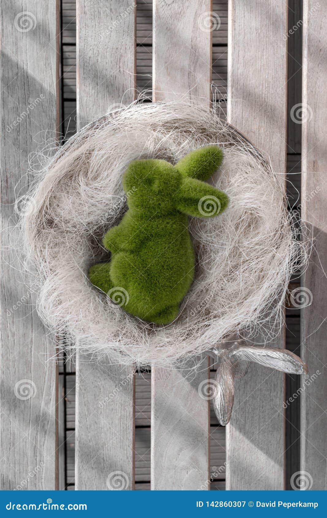 Conejito de pascua que miente en un arco, banco blanco del lavado, fondo de madera