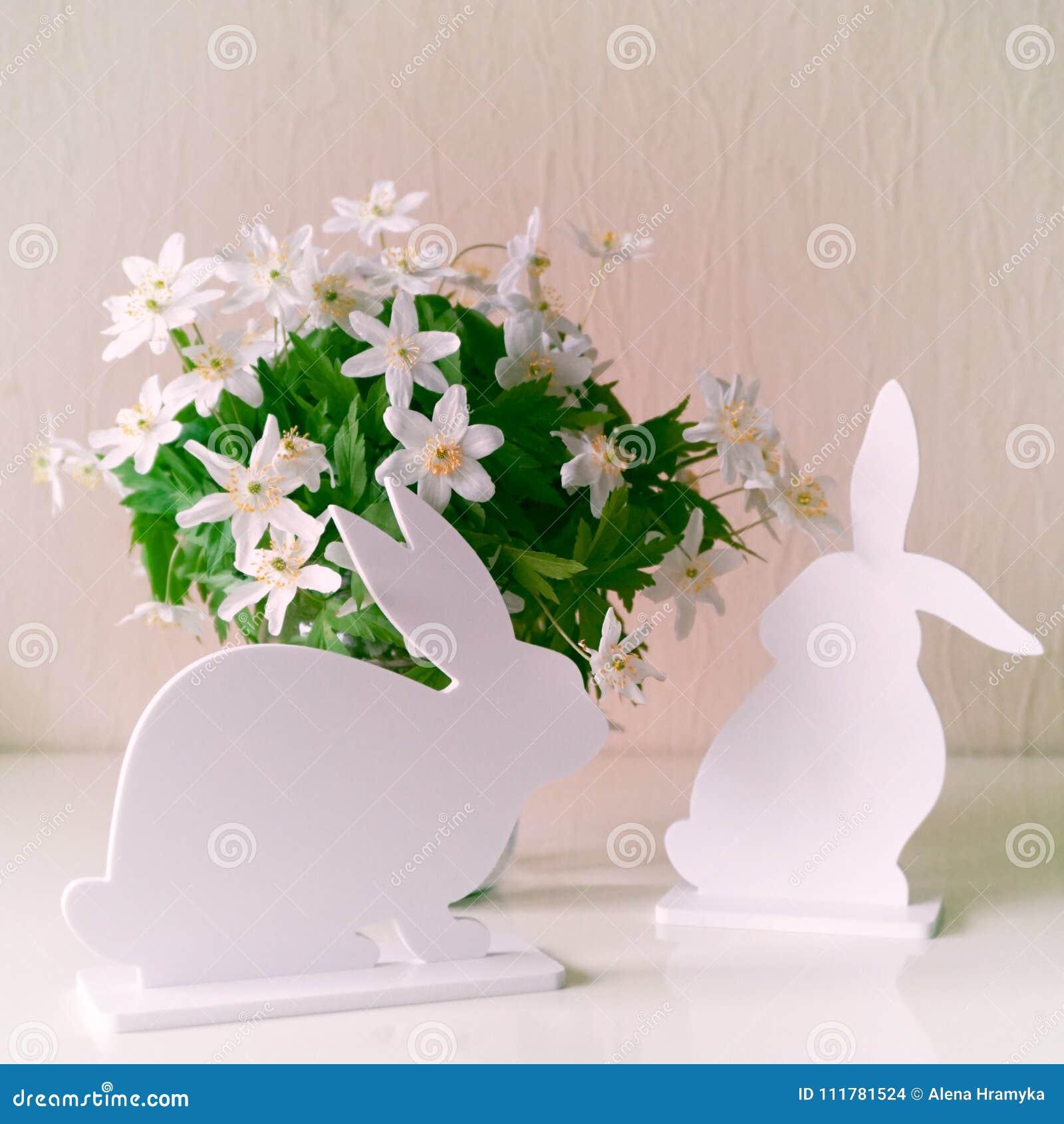 Conejitos de pascua con las flores de la primavera