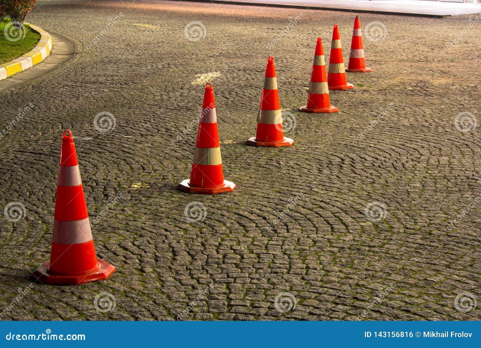 Cones da estrada no pavimento antes de entrar em algum lugar