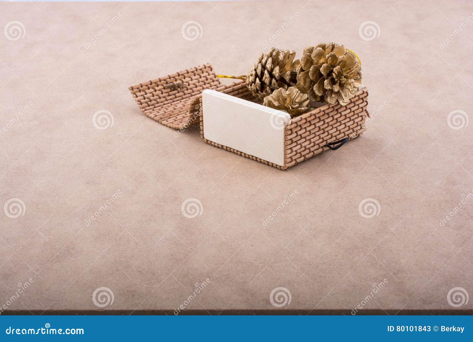 Cones do pinho em uma caixa de madeira da palha