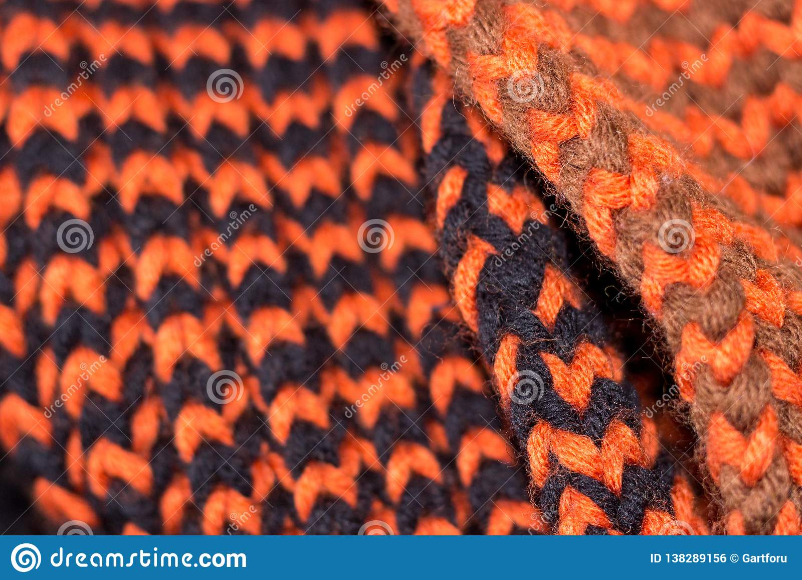Confecção de malhas Textura feita malha fundo Agulhas de confecção de malhas brilhantes Fio de lãs alaranjado e preto para fazer