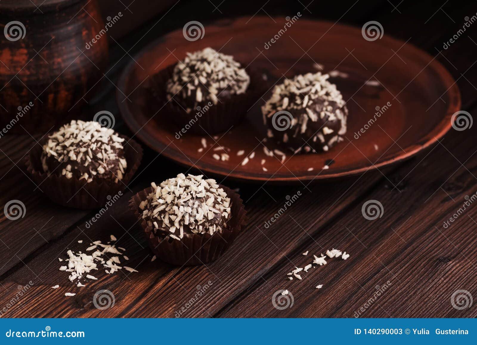 Confeitos do chocolate do close-up com coco em uma tabela de madeira rústica escura Doces caseiros Foco seletivo