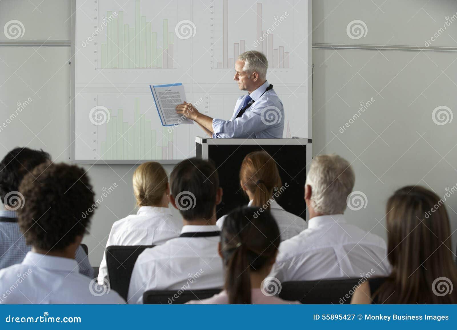 Conferencia envejecida centro de Delivering Presentation At del hombre de negocios