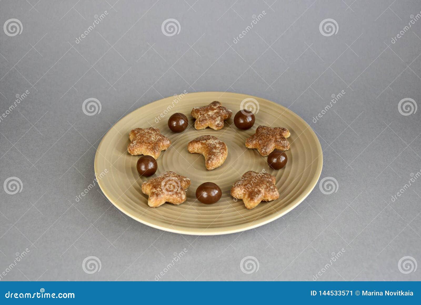 Confetteria, palle del cioccolato e biscotti su un piatto ceramico