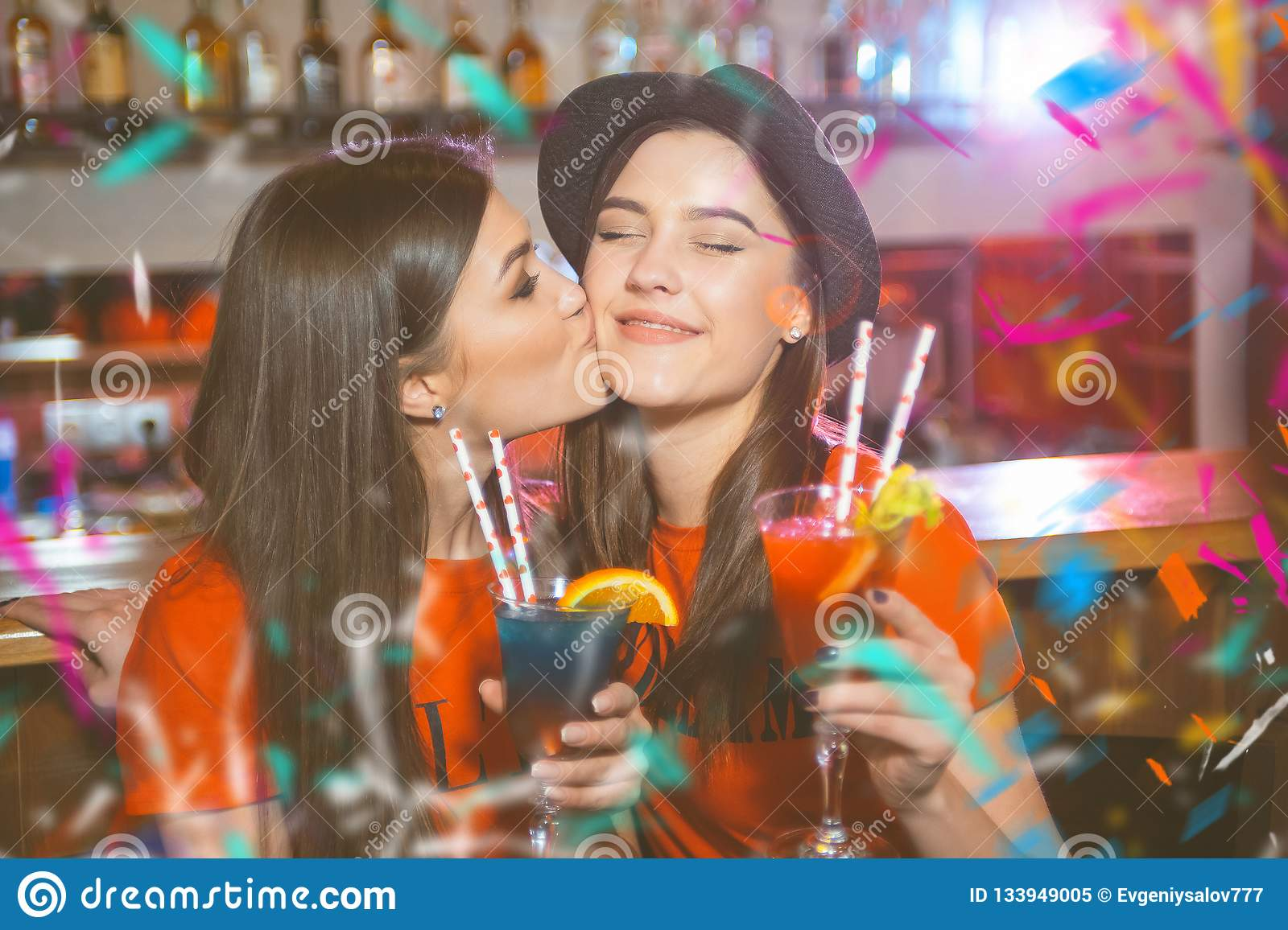 Two young lesbian girls kissing at a club party.