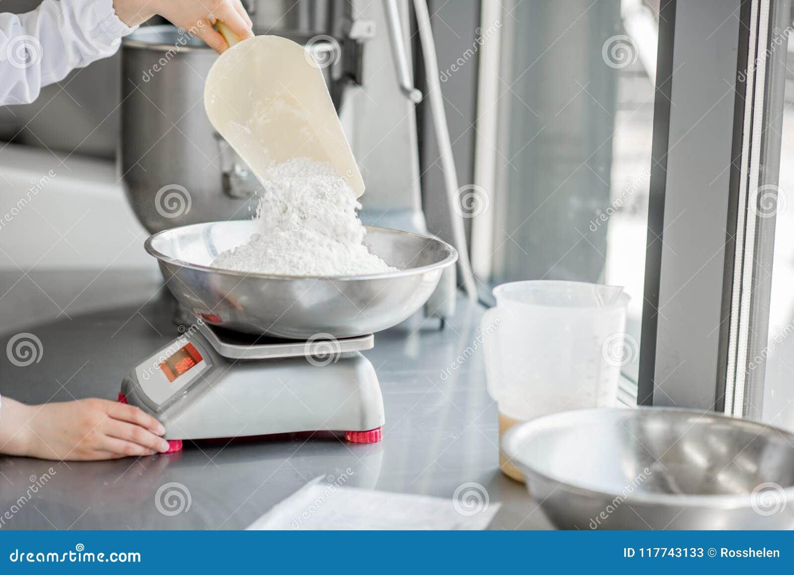 Confettiere della donna che lavora alla fabbricazione del forno