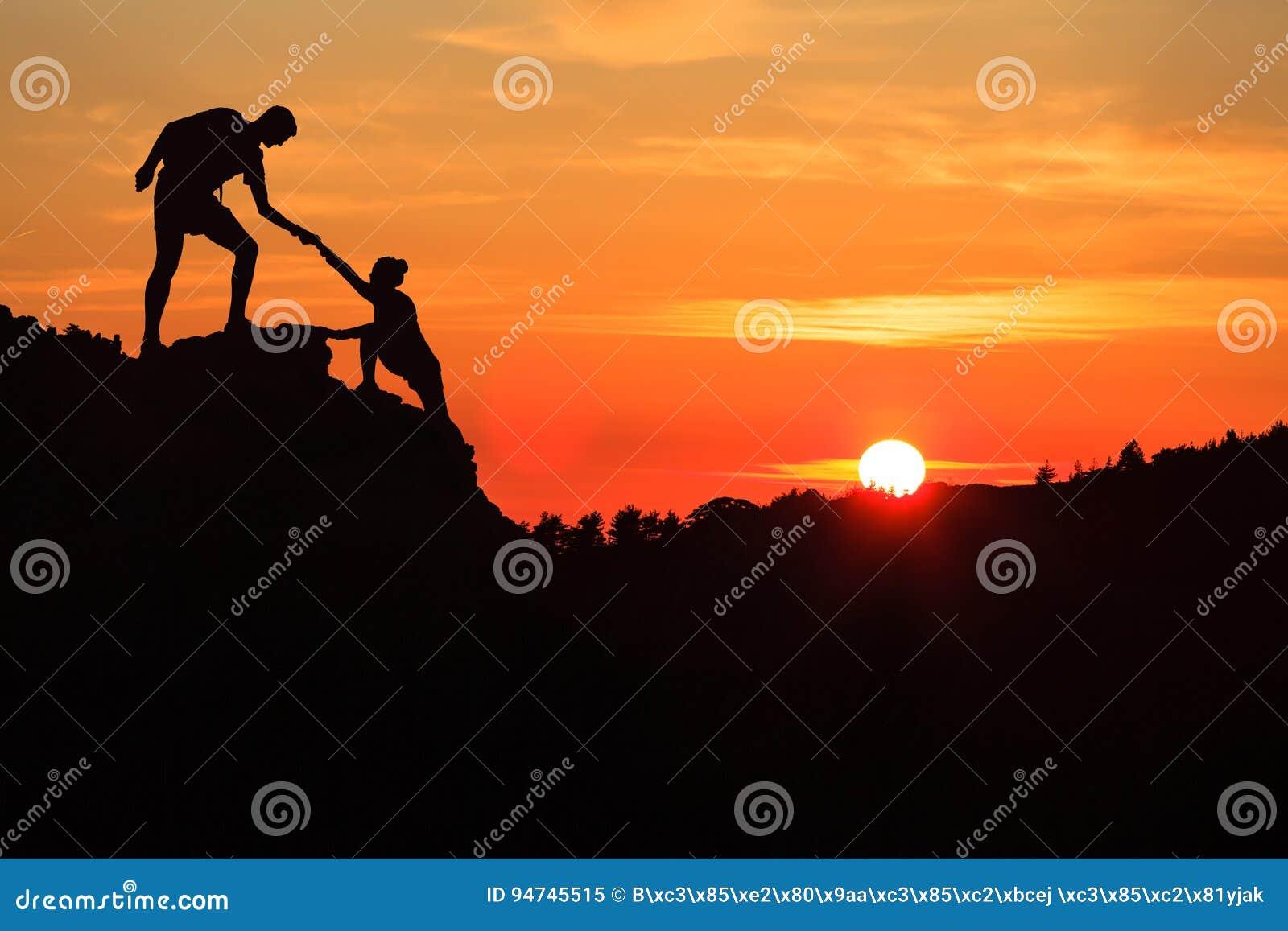 Confianza de la mano amiga de los pares del trabajo en equipo en montañas inspiradoras