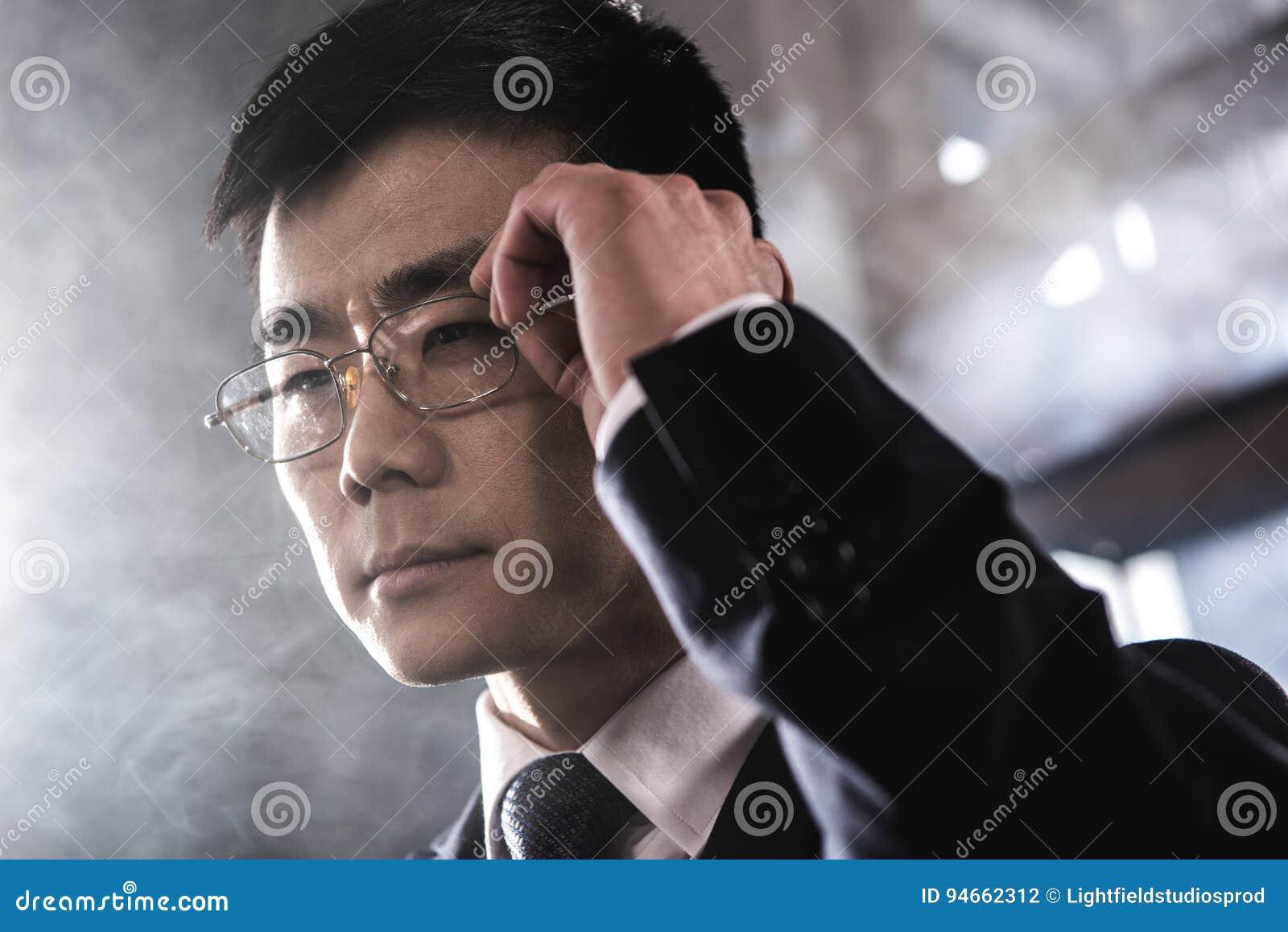 Confident asian businessman in eyeglasses looking away