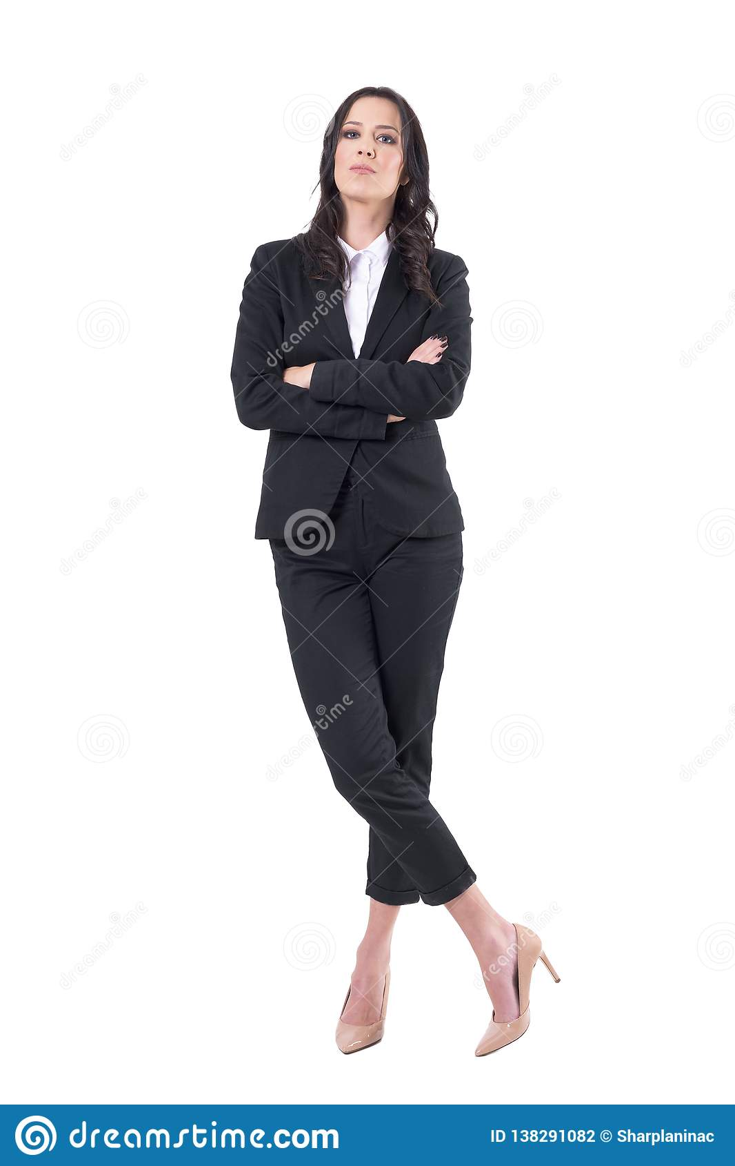 Confident business woman in black suit with crossed arms and crossed legs standing