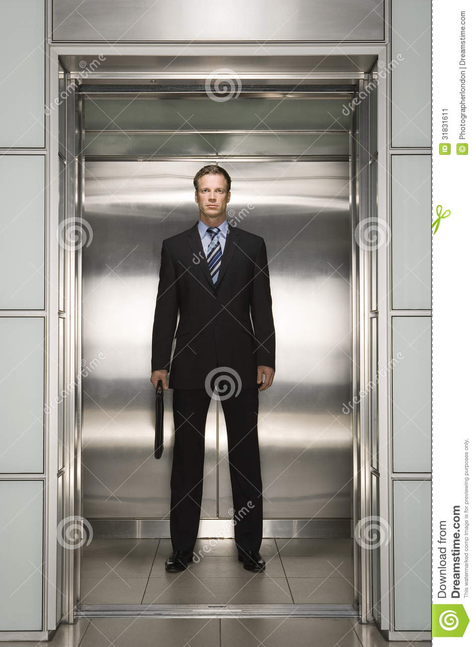 confident businessman with briefcase standing in elevator