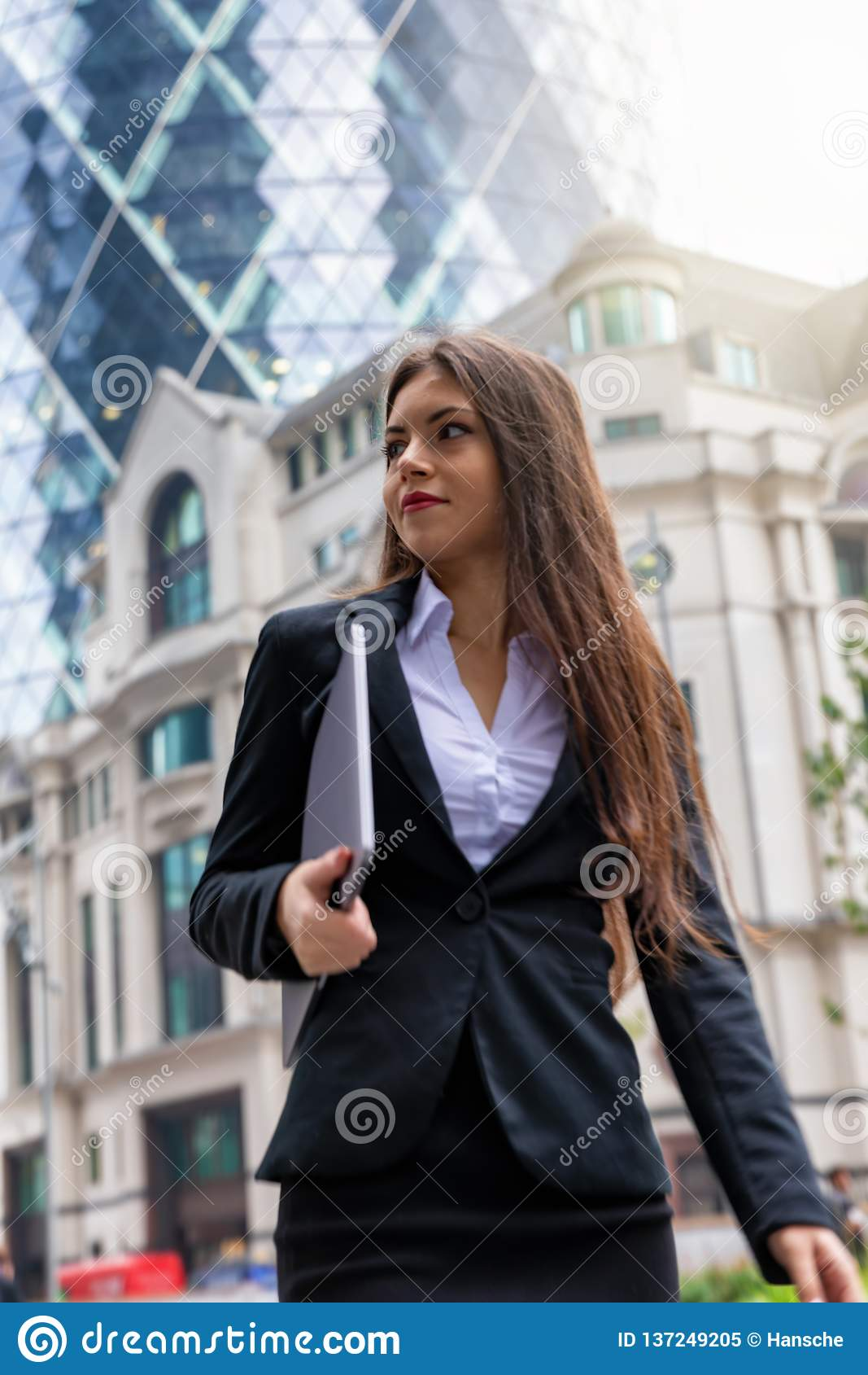 Confident businesswoman in corporate outfit walks outdoors in financial district