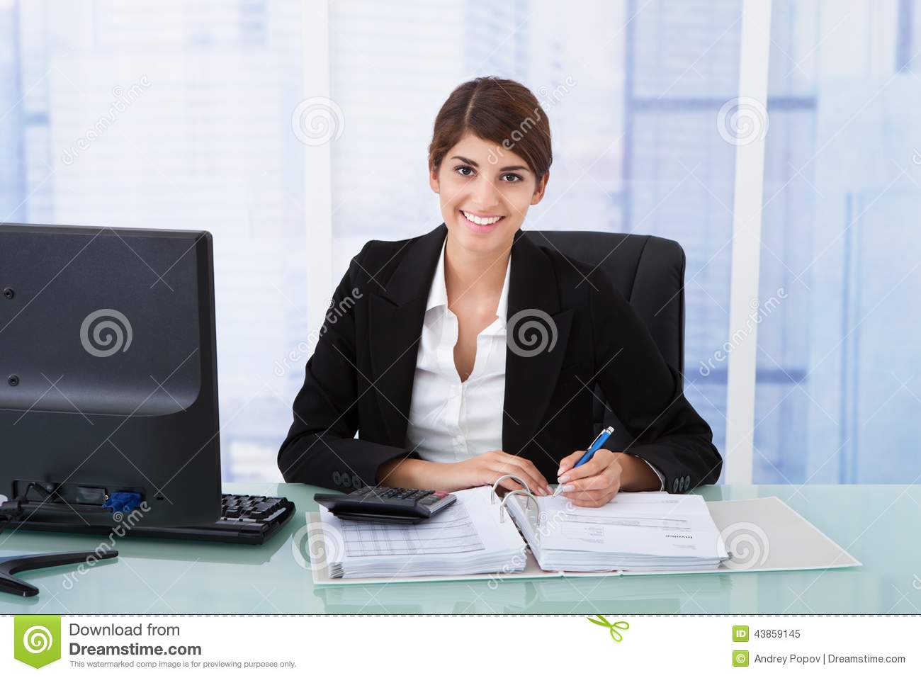Confident businesswoman using calculator at office desk