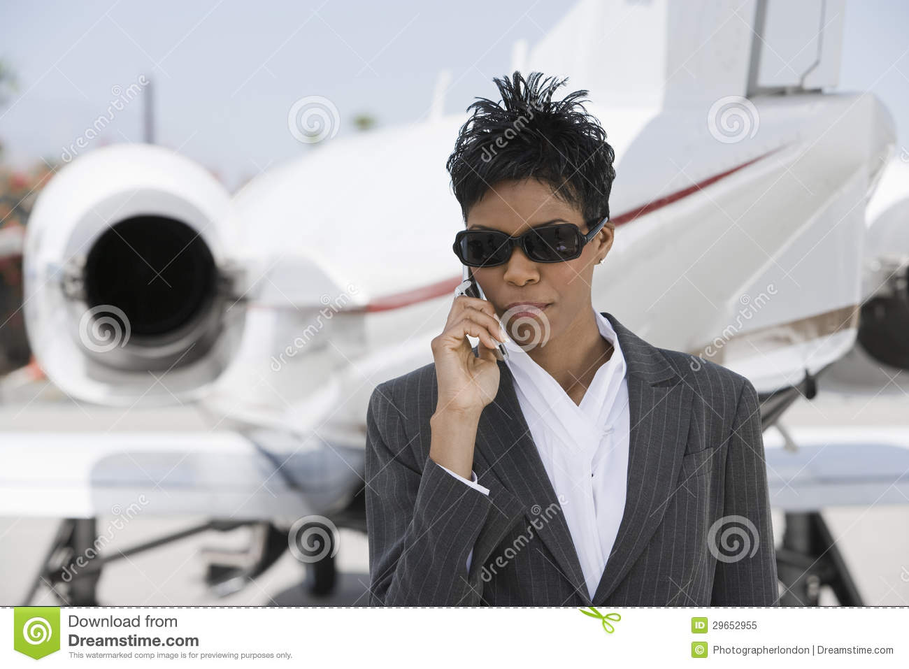 Confident Businesswoman Using Cellphone At Airfield