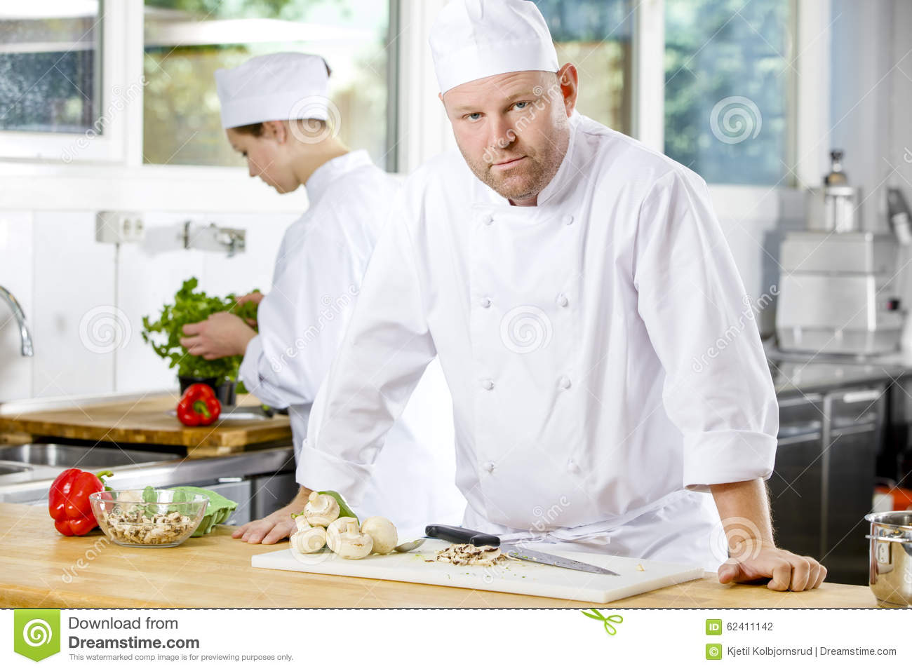 Confident chef making food in large kitchen