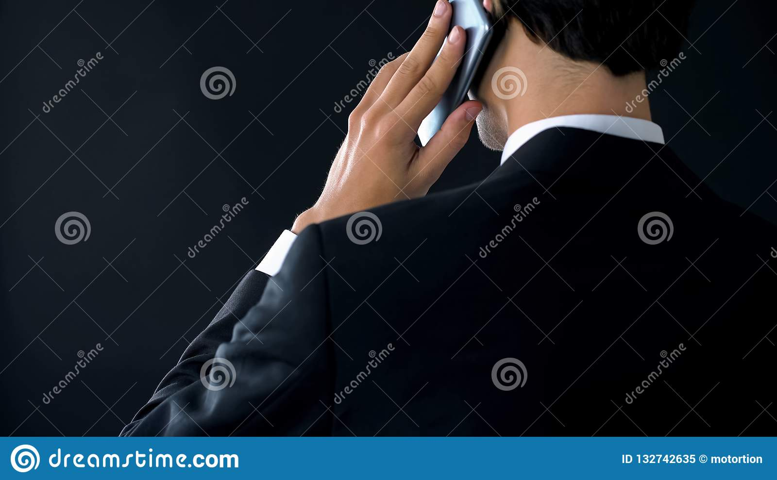 Confident company director talking phone back view, appointing partner meeting