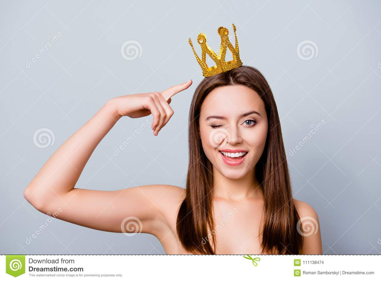 Confident cute beautiful young woman with a crown on her head is