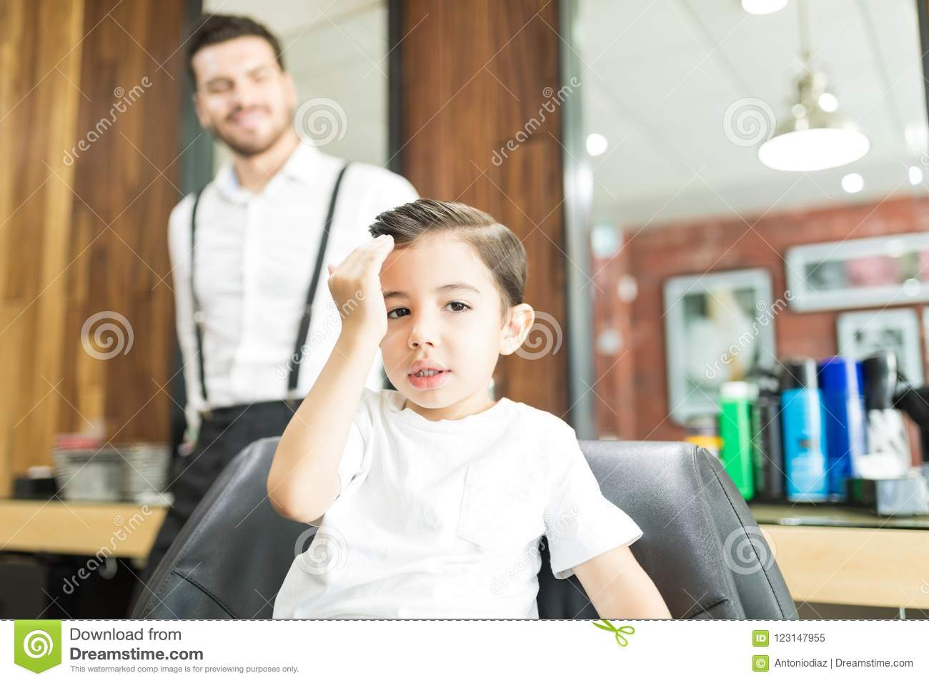 Fashionable Boy Touching Hair After Haircut In Barber Shop Stock