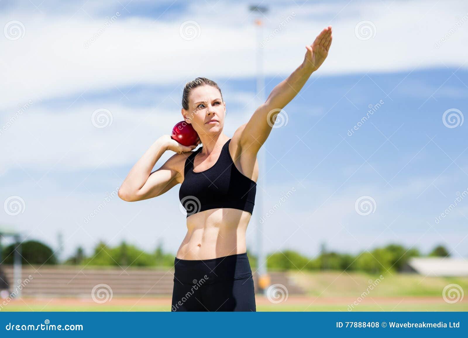 Confident female athlete preparing to throw shot put ball